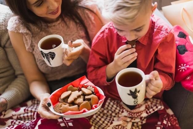 Concept de noël avec la mère et le garçon avec du thé et des biscuits