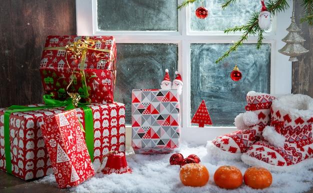 Concept de noël avec des pantoufles, des oranges et des cadeaux