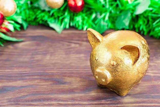 Concept de noël - symbole année cochon d'or se dresse sur une table en bois avec fond de branches d'arbres de noël