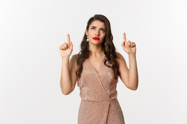 Concept de noël, vacances et célébration. femme élégante en robe de luxe à la recherche de logo douteux, pointant les doigts vers le haut, debout sur fond blanc.