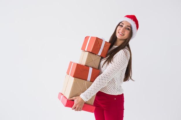 Concept de noël et vacances - femme en bonnet de noel avec de nombreux cadeaux sur un espace blanc avec copie espace