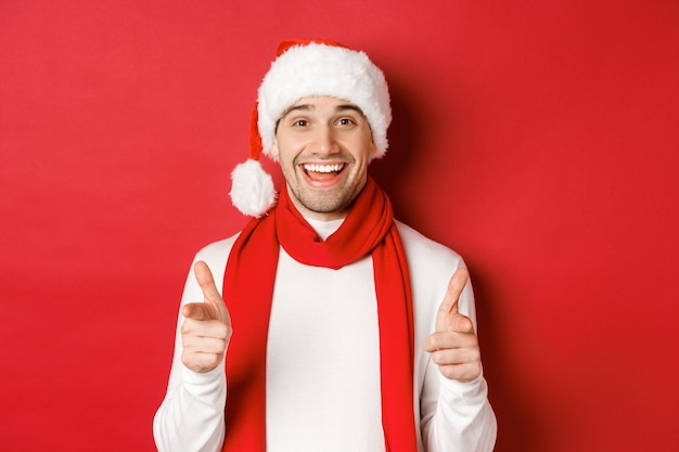 Concept de noël, vacances d'hiver et célébration. homme effronté en bonnet et écharpe, souriant et pointant du doigt la caméra, souhaitant une bonne année, debout sur fond rouge
