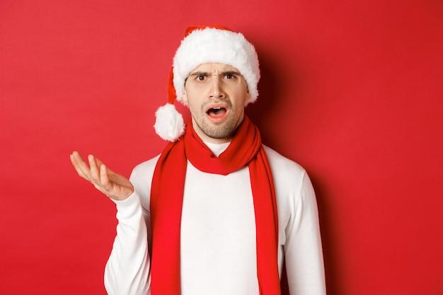 Concept de noël, vacances d'hiver et célébration. portrait d'un homme confus en bonnet et écharpe, fronçant les sourcils et l'air perplexe, debout sur fond rouge.