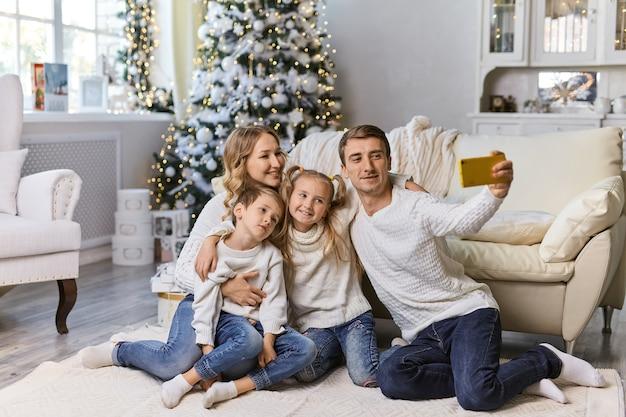 Concept de noël, vacances, technologie et personnes - famille heureuse assise dans le salon et prenant une photo de selfie avec un smartphone à la maison