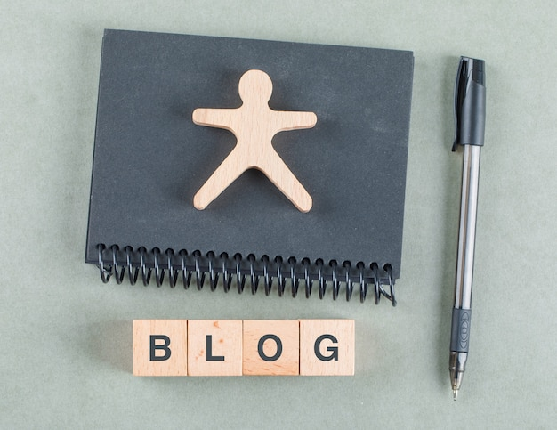 Concept de notes de blog avec des blocs en bois, stylo et vue de dessus de cahier noir.