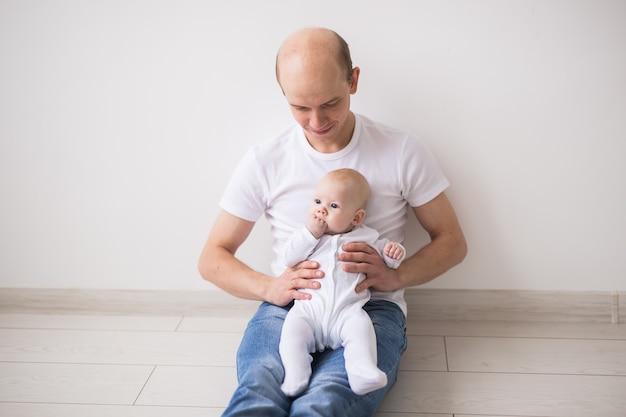 Concept de nourrisson, de famille et d'enfants - le père chauve prend soin de son petit bébé