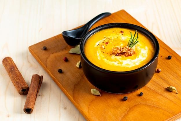 Concept de nourriture automne hiver soupe potiron ou butternut dans un bol noir sur fond en bois