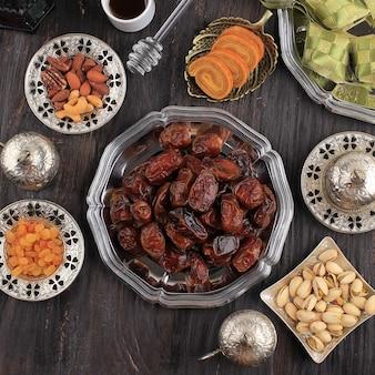 Concept de nourriture et de boisson de ramadan avec espace de copie sur table en bois. dattes fruits, noix, graines, café, thé, miel et ketupat. nourriture de style arabe musulman pour ied al fitr