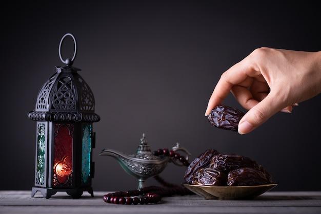Concept de nourriture et de boissons du ramadan. main de femme tend la main vers une assiette avec des dates