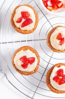 Concept de nourriture cupcake fraîchement confectionné à la crème et aux fraises maison sur backfround blanc