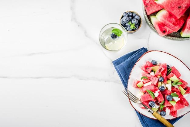 Concept de nourriture d'été, salade de pastèque froide fraîche avec fromage feta, myrtille, avocat et menthe, fond de marbre blanc