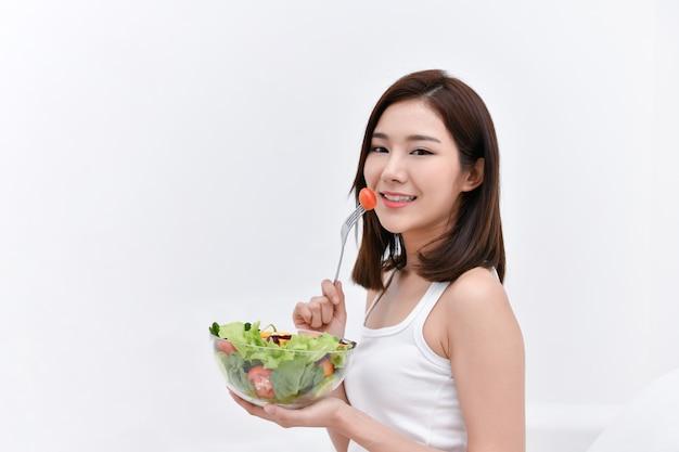 Le concept de nourriture nutritionnelle. belle fille prend soin de sa santé en mangeant des légumes.