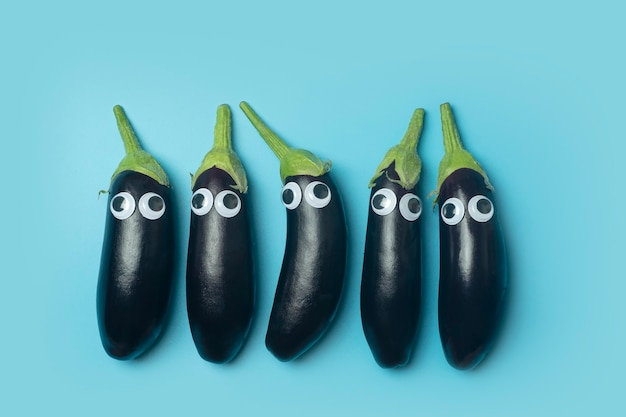 Concept de nourriture pour enfants. aubergine aux yeux sur fond bleu coloré. légumes drôles et nourriture pour enfants