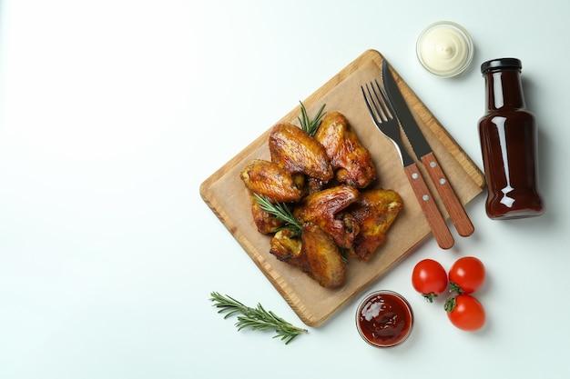Concept de nourriture savoureuse avec des ailes de poulet cuit au four sur fond blanc