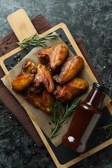 Concept de nourriture savoureuse avec des ailes de poulet cuit au four sur fond noir fumé