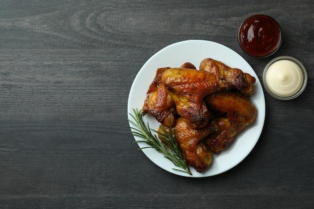 Concept de nourriture savoureuse avec des ailes de poulet cuit au four sur fond sombre, espace pour le texte