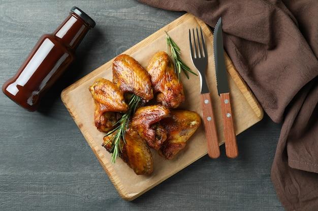 Concept de nourriture savoureuse avec des ailes de poulet cuit au four sur fond sombre