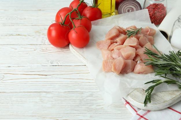 Concept de nourriture savoureuse avec des tranches de filet de poulet cru sur fond de bois blanc