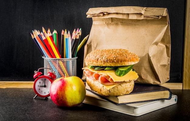 Concept de nourriture scolaire saine, sac en papier avec déjeuner, pomme, sandwich, livres et réveil sur tableau noir