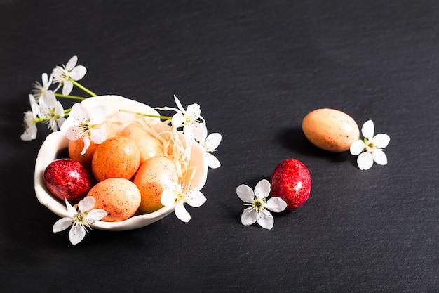 Concept de nourriture de vacances bonbons colorés et œufs de pâques au chocolat sur plaque d'ardoise noire