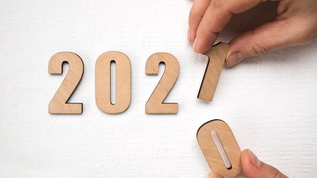 Concept de nouvel an 2021 avec main mettant des numéros en bois 2021 sur table en bois