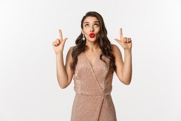 Concept de nouvel an, noël et célébration. belle femme curieuse en tenue de soirée, disant wow et regardant l'offre promotionnelle, pointant les doigts vers le haut, montrant une publicité.