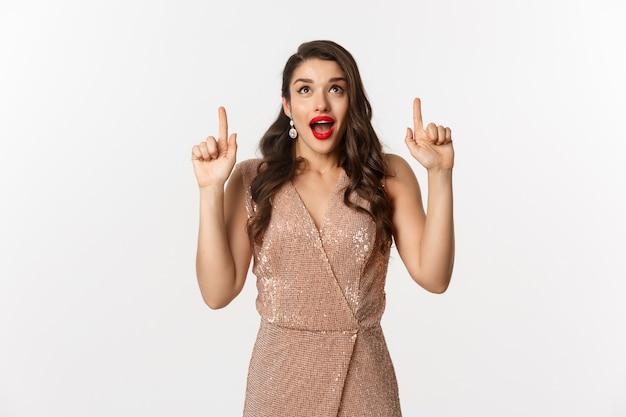 Concept de nouvel an, noël et célébration. excitée belle femme montrant une publicité, haletant étonné, vêtue d'une robe de soirée et pointant vers le haut, fond blanc