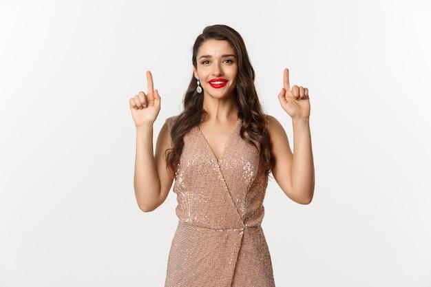 Concept de nouvel an, noël et célébration. femme élégante avec rouge à lèvres rouge, robe glamour, pointant les doigts vers le haut et montrant l'offre promotionnelle des vacances d'hiver, fond blanc