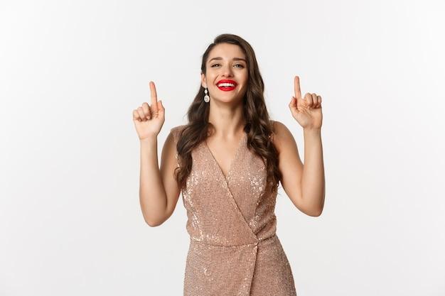 Concept de nouvel an, noël et célébration. femme magnifique et élégante montrant une publicité de vacances, pointant les doigts vers le haut, montrant une offre promotionnelle, debout sur fond blanc