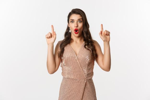 Concept de nouvel an, noël et célébration. femme surprise et excitée en robe glamour, portant une tenue pour la fête, pointant les doigts vers le haut, montrant une offre promotionnelle, fond blanc.
