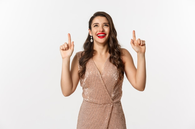 Concept de nouvel an, noël et célébration. heureuse femme élégante en robe de soirée, riant et levant les yeux, pointant vers l'offre promotionnelle supérieure, fond blanc.