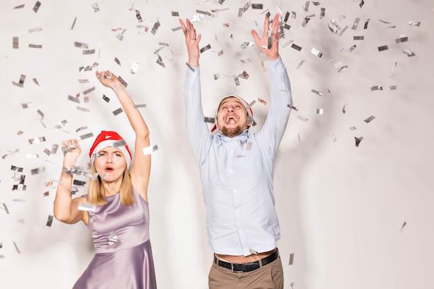 Concept de nouvel an, de noël et de fête - des jeunes joyeux se sont arrosés de confettis sur fond blanc.