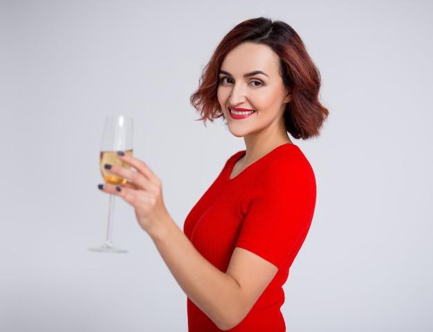 Concept de nouvel an - portrait de jeune femme posant avec une coupe de champagne sur fond blanc