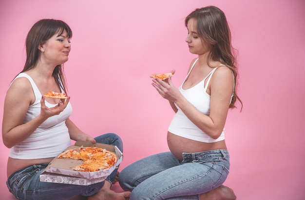 Concept de nutrition, les femmes enceintes, manger de la pizza sur un mur rose