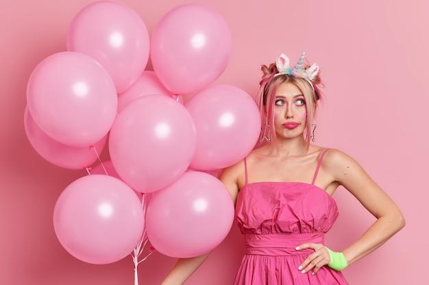 Concept D'occasion Spéciale. Femme Blonde Pensive Regarde Pensivement De Côté Garde La Main Sur La Taille Photo gratuit