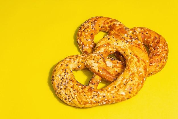 Concept de l'oktoberfest - bretzels isolés sur fond jaune. une lumière dure à la mode, une ombre sombre, un espace de copie