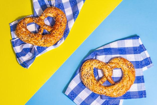 Concept d'oktoberfest - bretzels sur une serviette traditionnelle. lumière dure à la mode, ombre sombre. fond jaune-bleu pastel, vue de dessus