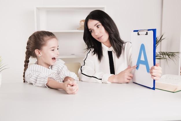 Concept d'orthophonie. enfant avec thérapeute apprenant des lettres ensemble.