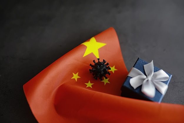 Le concept de la pandémie mondiale de coronavirus. la situation géographique du virus. drapeau de la chine et modèle de virus et boîte-cadeau.