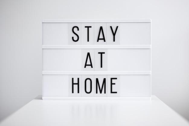 Concept de pandémie et de quarantaine de coronavirus - caisson lumineux avec message de séjour à la maison sur fond blanc