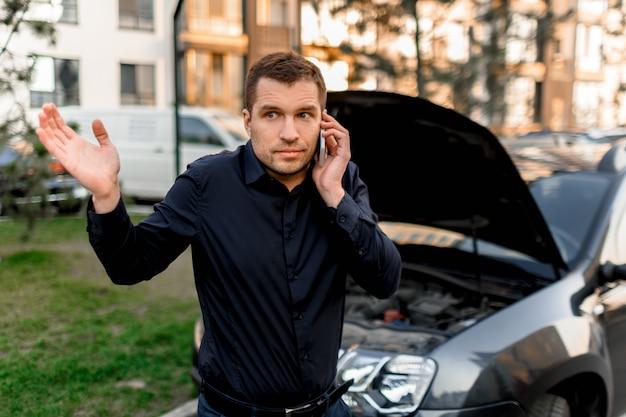 Concept de panne de voiture. la voiture ne démarre pas. un jeune homme demande un service de voiture. ils ne peuvent pas réparer eux-mêmes la voiture. l'assurance doit couvrir tous les frais.