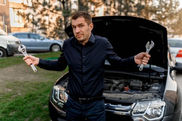 Concept de panne de voiture. la voiture ne démarre pas. le jeune homme essaie de tout réparer lui-même, mais il ne sait pas quoi faire. ils ne peuvent pas réparer eux-mêmes la voiture. l'assurance doit couvrir tous les frais.
