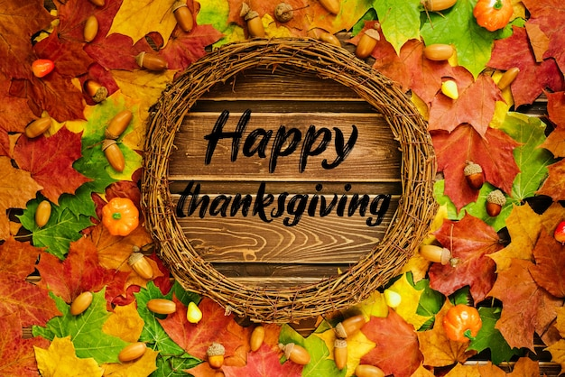 Le concept de papier peint d'automne. feuilles d'érable séchées et glands bordés d'un cadre rond avec texte : happy thanksgiving.