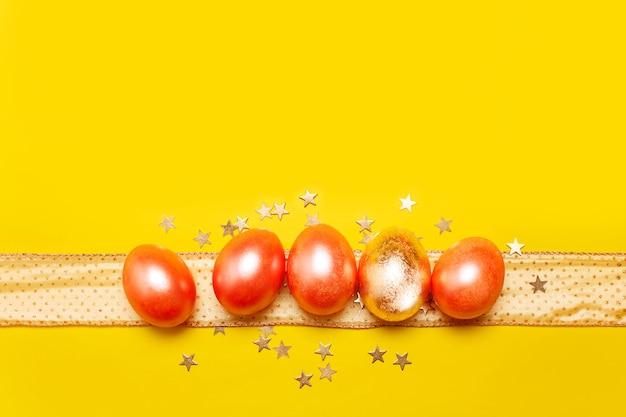 Concept de pâques avec cinq oeufs roses et dorés colorés