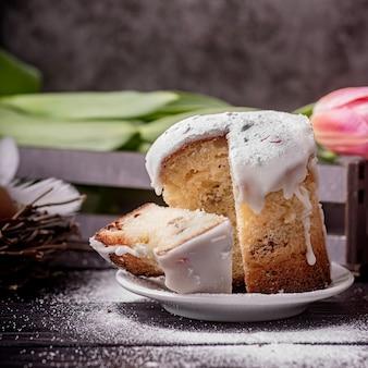 Concept de pâques. cuisson et cuisson. gâteau de pâques glacé avec des tulipes sur fond rustique foncé