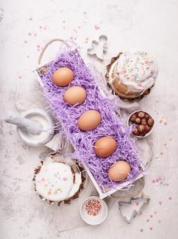 Concept de pâques. cuisson et cuisson. oeufs de pâques dans une boîte en bois blanche décorée de gâteaux glacés et d'ustensiles de cuisine