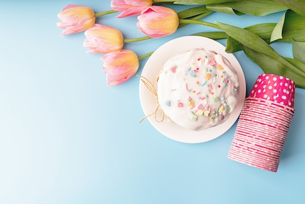 Concept de pâques. gâteau de pâques avec des tulipes sur fond bleu vue de dessus à plat avec copie espace
