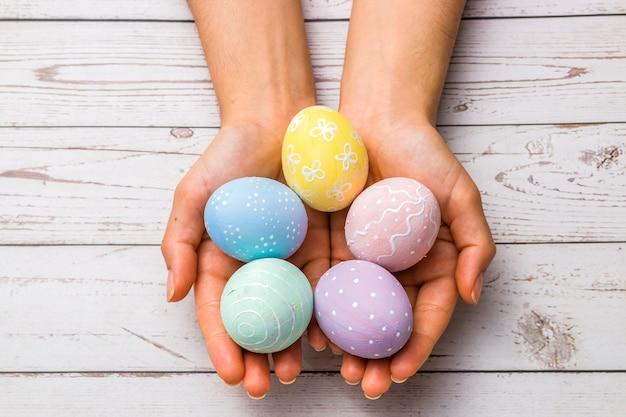 Concept de pâques. gros plan de belles mains de femme tenant des oeufs de pâques peints à la main dans des couleurs pastel tendres sur une table en bois