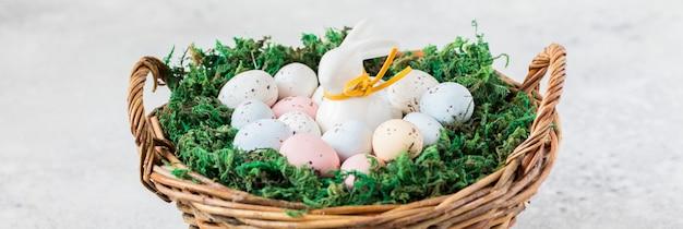 Concept de pâques. lapin dans un panier avec des oeufs de pâques colorés.