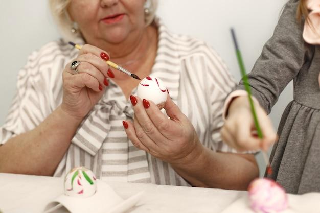 Concept de pâques. petite fille et sa grand-mère colorant des œufs pour pâques.